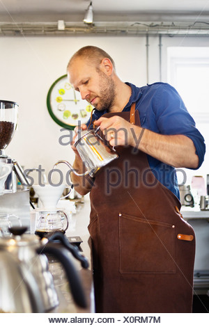 Male barista pouring boiling water into coffee filter - Stock Photo