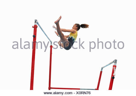 Young gymnast performing on uneven bars - Stock Photo