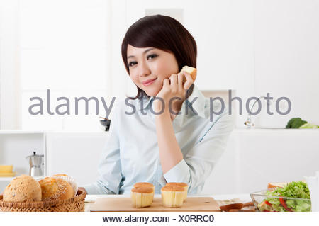 Young woman holding bread and looking down with smile, - Stock Photo