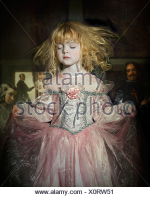A young girl with blonde hair dressed in a pink period costume with painted figures in the background - Stock Photo