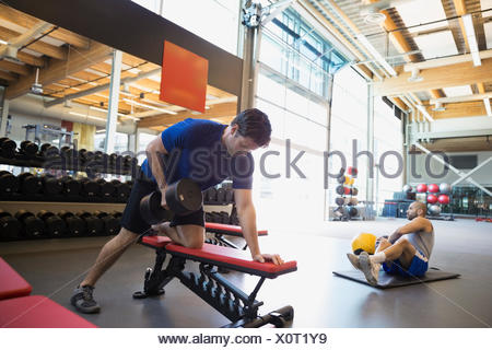 Man doing dumbbell rows on bench at gym - Stock Photo