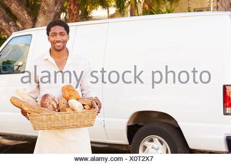 Baker Delivering Bread Standing In Front Of Van - Stock Photo