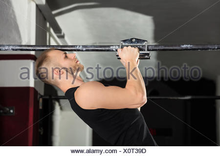 An Athlete Man Doing Narrow Grip Pullup Exercise - Stock Photo