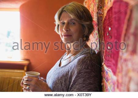 Portrait confident senior woman drinking coffee - Stock Photo