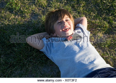 Portrait of boy lying on park grass and laughing - Stock Photo
