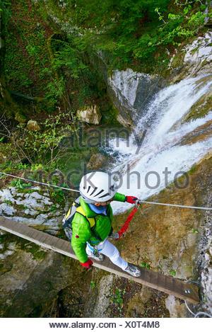 climber on suspension bridge at a waterfall, Via Ferrata Saint Vincent de Mercuze, France, Montalieu - Stock Photo