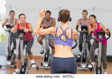 Trainer and fitness class at spinning class - Stock Photo