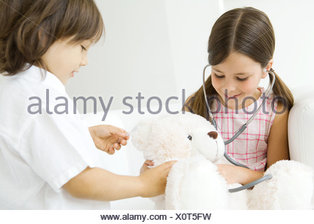 Two children playing doctor, girl listening to teddy bear's heart with stethoscope - Stock Photo