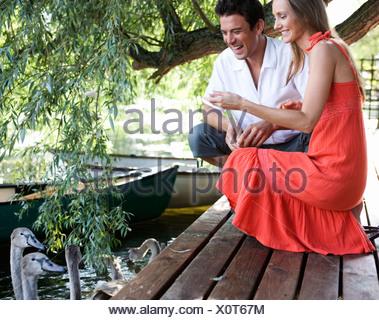 Young couple feeding swans - Stock Photo