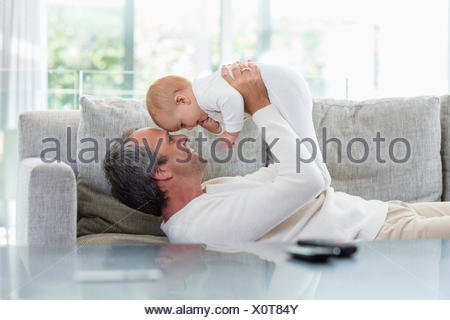 Happy father playing with his cute baby daughter at home - Stock Photo