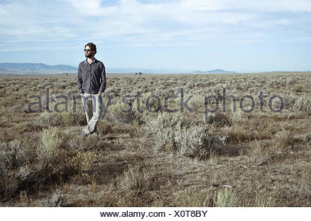 USA, Man standing in sagebrush - Stock Photo