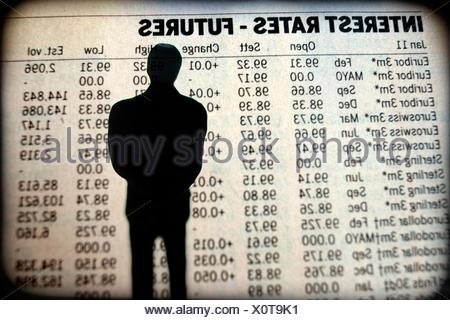 human silhouette watching the interest rates grafic. - Stock Photo
