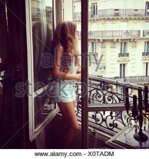 Side View Of Young Woman Looking Through Window - Stock Photo