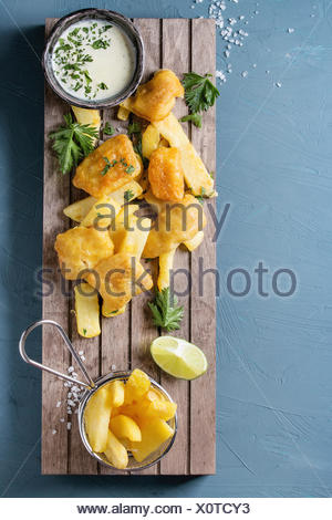 Traditional british fast food fish and chips. Served with white cheese sauce, lime, parsley, french fries in frying basket on wooden serving board ove - Stock Photo