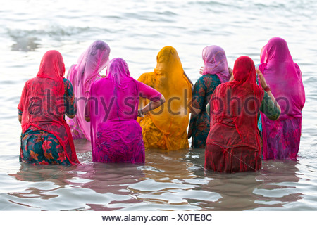 Hindu pilgrims, women in colourful saris taking a holy bath om the sea before sunrise, at the Ghat Agni Theertham - Stock Photo