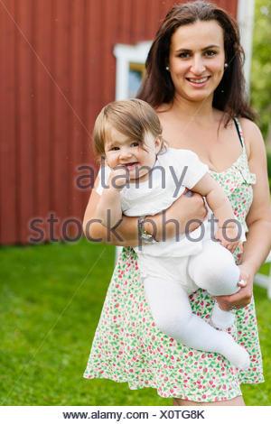 Sweden, Varmland, Filipstad, Gasborn, Horrsjon, Portrait of mother holding baby girl (12-17 months) - Stock Photo
