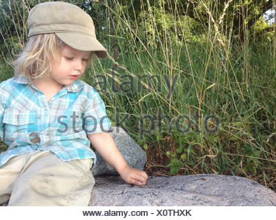 Young Boy Playing On A Rock - Stock Photo