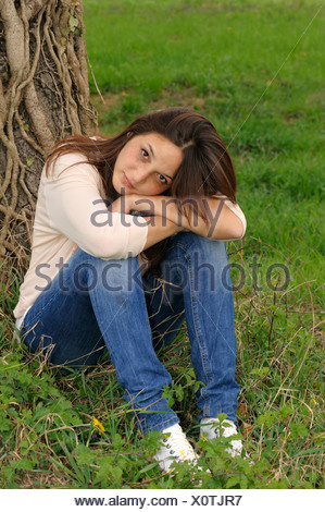 Thoughtful young woman of Indonesian origin, portrait, sitting in front of a tree trunk, PublicGround - Stock Photo