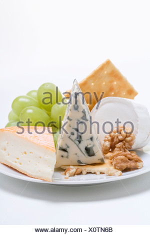 Cheese plate with crackers, nuts and grapes - - Stock Photo