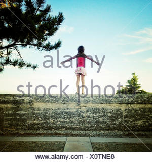 Rear view of girl standing on wall with her arms outstretched - Stock Photo