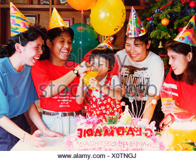 Happy family at little girl child's 4th birthday party. - Stock Photo