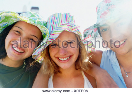 Three young girls in a row wearing sunhats looking at  camera and smiling. - Stock Photo