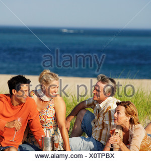 Two mature couples sitting on the beach - Stock Photo