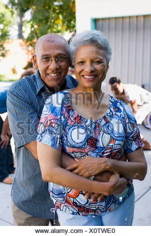 Couple embracing outdoors with family in background - Stock Photo