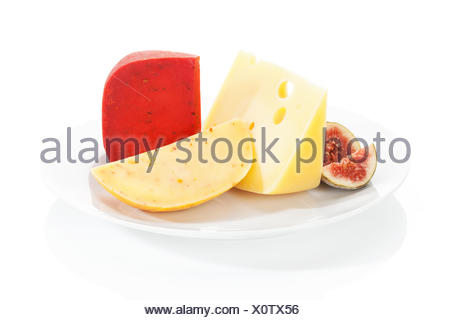 Luxurious cheese assortment with fig on white plate. Gouda chili, swiss cheese and gouda. Culinary eating. - Stock Photo
