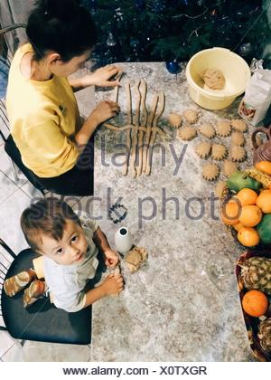 High Angle View Of Son Helping Mother In Preparing Food On Table - Stock Photo