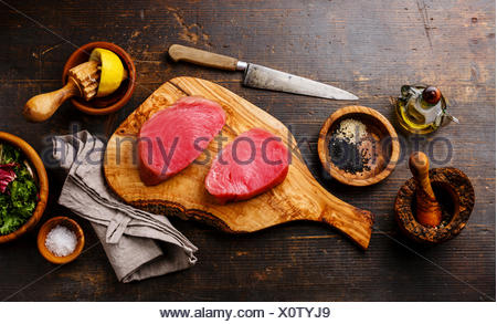 Raw tuna steaks fillet with lemon and sesame on olivewood cutting board on dark wooden background - Stock Photo
