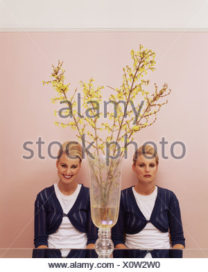 Two women sitting at table with a vase - Stock Photo