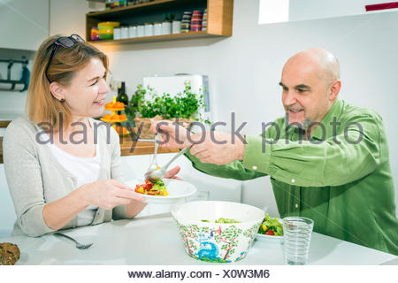 Senior couple eating together in kitchen - Stock Photo