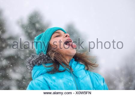Girl looking up, sticking out tongue catching snowflakes - Stock Photo
