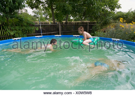 Wroclaw, Poland, family splashing in the water in the inflatable pool in the garden - Stock Photo