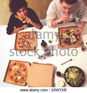 Overhead View Of People Having Pizzas At Table - Stock Photo
