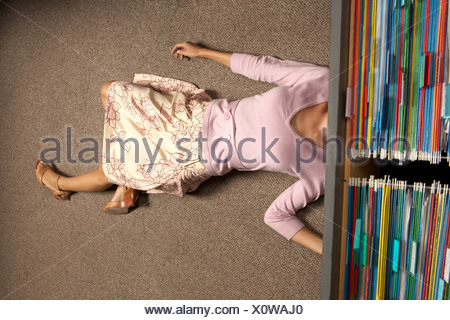 High angle view of a businesswoman lying under a filing cabinet drawer - Stock Photo