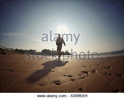 Silhouette of man running on beach - Stock Photo