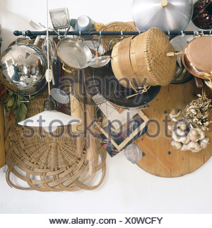 Selection of mismatched kitchen equipment hanging on a rail, including utensils, bamboo steamer, rolling pin, garlic bulbs and - Stock Photo