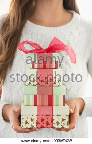 Woman holding stack of Christmas boxes - Stock Photo