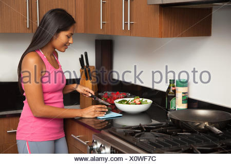 Woman preparing salad in kitchen - Stock Photo