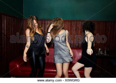 Three adult female friends dancing in club on night - Stock Photo