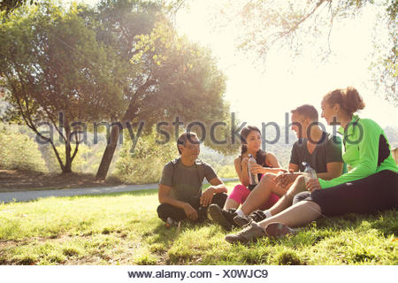 Four mature male and female runners sitting chatting in park - Stock Photo