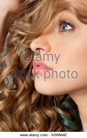 Close-up of beautiful blond woman with pierced nose looking away - Stock Photo