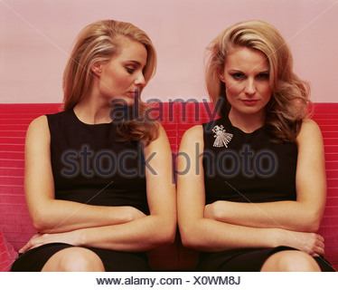 Woman looking jealously at another woman's brooch - Stock Photo