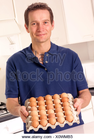 MAN IN KITCHEN WITH TRAY OF EGGS - Stock Photo