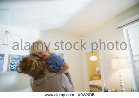Affectionate mother and daughter hugging living room - Stock Photo