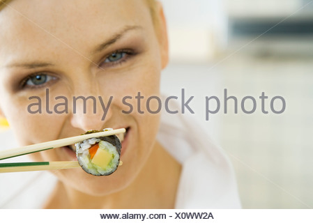 Woman holding sushi roll with chopsticks, smiling - Stock Photo