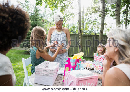 Woman touching stomach of pregnant friend baby shower - Stock Photo