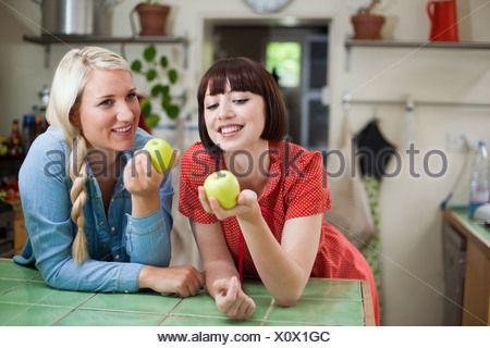 Two young women in kitchen holding apples - Stock Photo